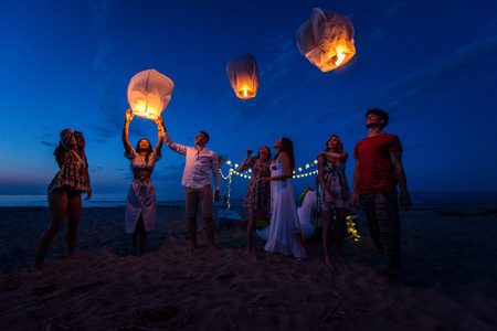 Young millenials holding and igniting sky lantern - Lantern festival on the beach
