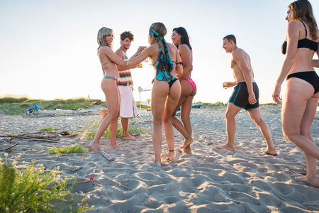 Happy group of friends celebrating and having fun on the beach - Young people on summer holiday