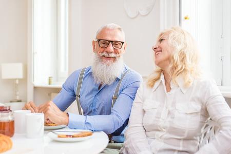 Glückliches älteres Paar, das zu Hause frühstückt - Ehepaar in den 60ern in ihrer Wohnung, Konzepte über Dienstalter und Beziehung