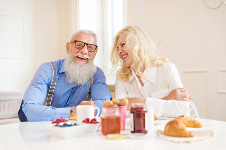 Happy senior couple having breakfast at home - Married couple on the 60s in their apartment, concepts about seniority and relationship