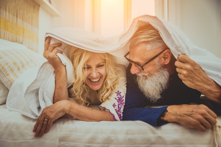 Senior couple in the 60's having fun at home - Cheerful married couple portrait, concepts about seniority and relationship
