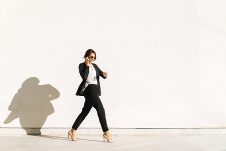 Beautiful businesswoman walking outdoors - Pretty young adult female 스톡 콘텐츠