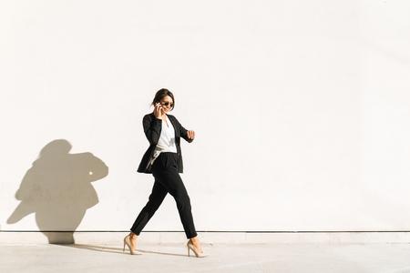 Beautiful businesswoman walking outdoors - Pretty young adult female Standard-Bild