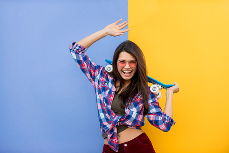 Porträt des stilvollen hübschen Mädchens auf farbigem Hintergrund - glückliche Frau mit städtischer Kleidung, Konzepte über Lebensstil und Jugend Standard-Bild