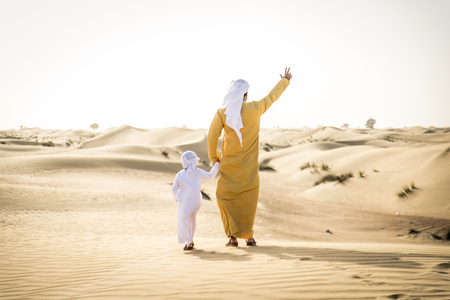 Happy family playing in the desert of Dubai -  Playful father and his son having fun outdoors Stock Photo