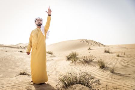 Handsome arabian man with traditional dress in the desert of Dubai Archivio Fotografico - 109820228