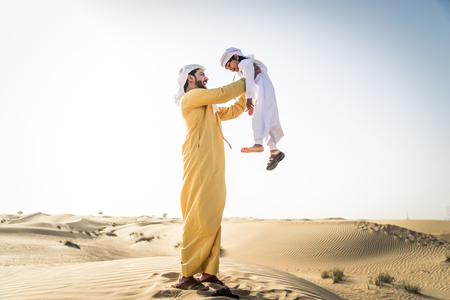 Happy family playing in the desert of Dubai -  Playful father and his son having fun outdoors Imagens
