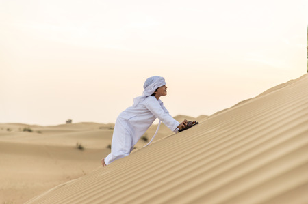 Happy kid playing in the desert of Dubai