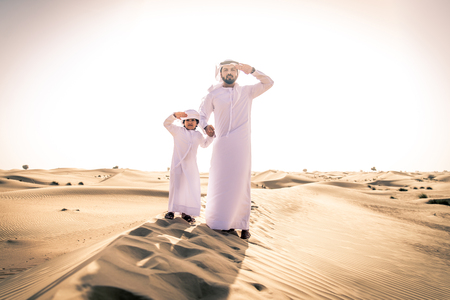 Happy family playing in the desert of Dubai -  Playful father and his son having fun outdoors Reklamní fotografie - 108943204