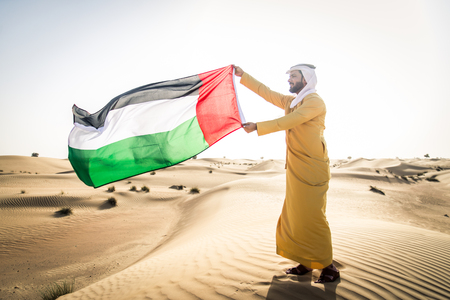Handsome arabian man with traditional dress in the desert of Dubai