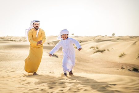 Happy family playing in the desert of Dubai -  Playful father and his son having fun outdoors Фото со стока