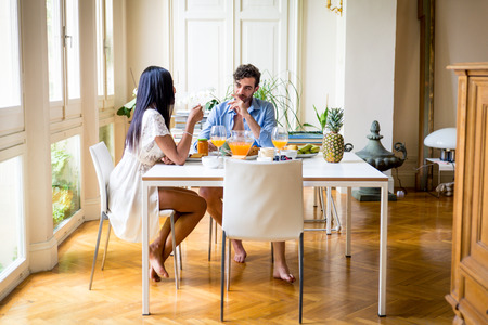 Happy couple having healthy breakfast at home in the morning - Happy moments of domestic partnership
