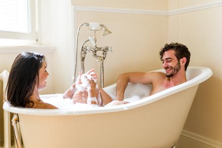 Pareja joven alegre en casa - momentos íntimos, pareja bañándose