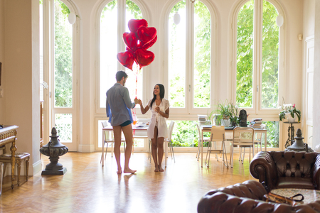 Romantic moments at home, boyfriend presenting heart shaped balloons to his girlfriend