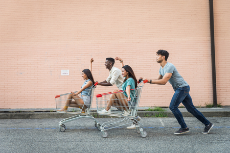 Multi-ethnic group of friends playing with shopping carts in a parking