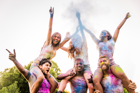 Group of happy friends playing with holi colors in a park - Young adults having fun at a holi festival, concepts about fun, fun and young generation