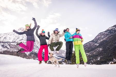 Felice gruppo di persone che si divertono in vacanza invernale - Amici con la tuta da neve che fanno festa all'aperto