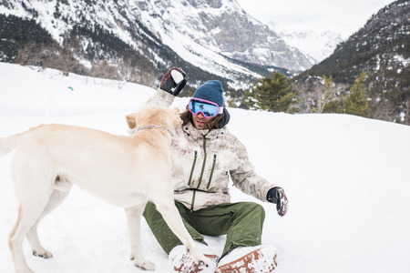 Owner and his dog playing in the snow - Young adult man having fun with his loyal labrador