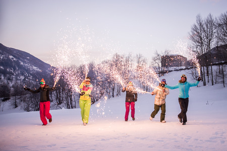 Happy group of people having fun on winter vacation - Friends with snow suit partying outdoors