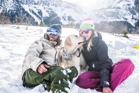 Happy couple playing and having fun with their loyal dog in the snow Фото со стока