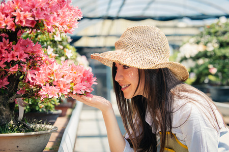 Pretty female gardener taking care of plants in her flowers and plants shop - Asian woman working in a greenhouse Stock fotó