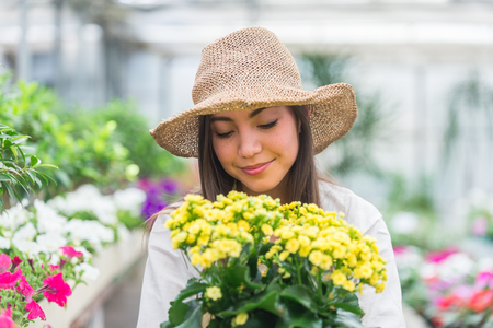 Pretty female gardener taking care of plants in her flowers and plants shop - Asian woman working in a greenhouse Foto de archivo - 109903986