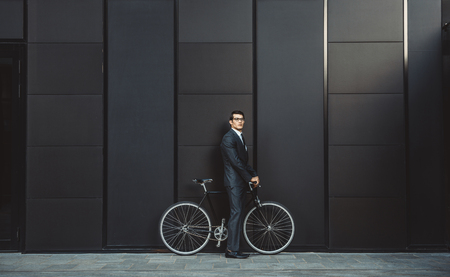 Young handsome man with business suit driving bycicle - Corporate businessman portrait, concepts about business, mobility and lifestyle