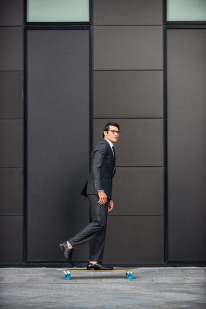 Young handsome man with business suit riding on a longboard - Corporate businessman portrait, concepts about business, mobility and lifestyle