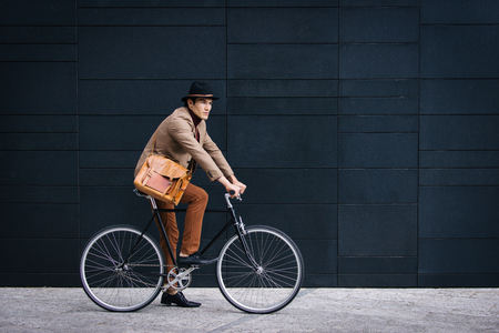 Young handsome man with casual clothes driving bycicle - Young student portrait, concepts about business, mobility and lifestyle