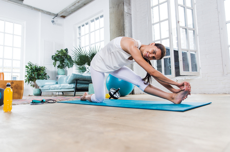 Beautiful girl making training and yoga at home in the morning Stock Photo