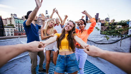 Group of friends spending time together on a rooftop in New york city, lifestyle concept with happy people