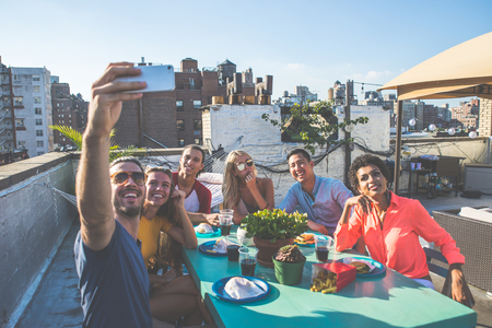 Group of friends spending time together on a rooftop in New York city, lifestyle concept with happy people Stok Fotoğraf