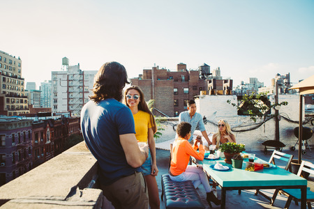 Group of friends spending time together on a rooftop in New York city, lifestyle concept with happy people Banco de Imagens