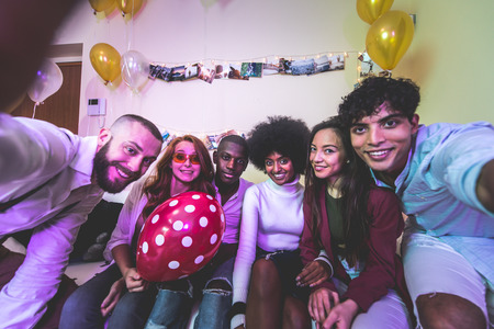 A group of young people celebrating and making party at home
