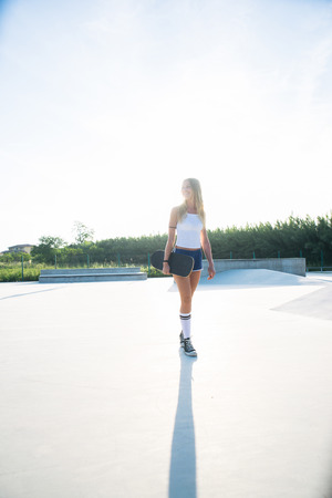 Stylish young woman skating outdoors - Pretty female skater playing with her skate