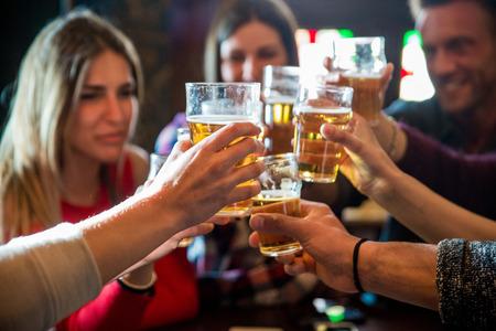 Groep gelukkige vrienden die feest hebben in een bar - Jongeren die bier drinken