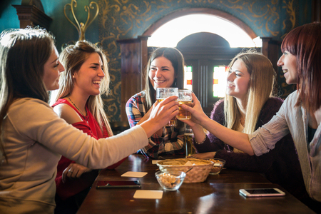 Group of happy friends having party in a bar  - Young people drinking beer