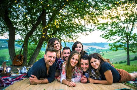 Gruppe von Freunden beim Grillen in der Natur - Glückliche Leute, die Spaß bei einem Picknick auf dem Land haben Standard-Bild