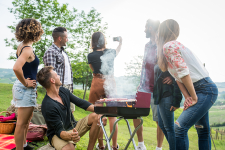 Group of friends making barbecue in the nature - Happy people having fun on a picnic in the countryside