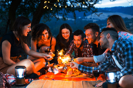 Group of young happy friends having picnic outdoors - People having fun and celebrating while grilling at a barbecue party in a countryside
