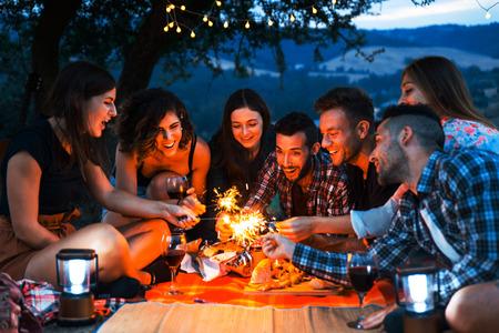 Groupe de jeunes amis heureux pique-niquant à l'extérieur - Des gens s'amusant et faisant la fête en grillant lors d'un barbecue dans une campagne Banque d'images
