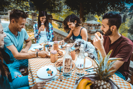 Happy cheerful  group of friends having breakfast in a farmhouse - Young people eating in the garden, concepts about healthy lifestyle and food