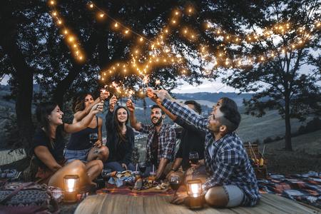 Groupe d'amis faisant un barbecue dans la nature - Des gens heureux s'amusant lors d'un pique-nique à la campagne Banque d'images