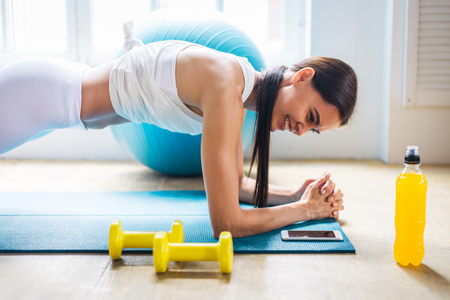 Athletic beautiful woman training at home - Young girl doing fitness in her apartment, concepts about fitness, sport and health 스톡 콘텐츠 - 111673234