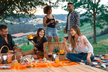 Groupe de jeunes amis heureux pique-niquant à l'extérieur - Des gens s'amusant et faisant la fête en grillant lors d'un barbecue dans une campagne
