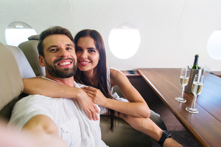Happy couple travelling on a luxury private jet - Young adults travel on a first class flight, concepts about travel and lifestyle