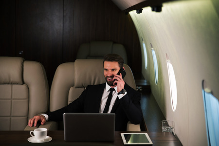Businessman working while travelling on private jet - Portrait of business people taking a first class flight for work, concepts about business and mobility