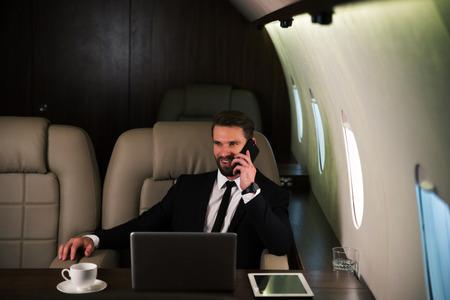 Uomo d'affari che lavora mentre viaggia su jet privato - Ritratto di uomini d'affari che prendono un volo di prima classe per lavoro, concetti su affari e mobilità