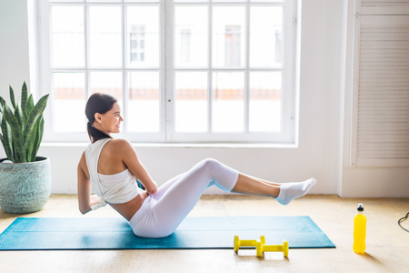 Athletic beautiful woman training at home - Young girl doing fitness in her apartment, concepts about fitness, sport and health