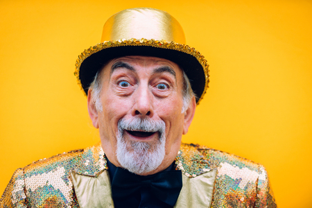 Funny and extravagant senior man posing on colored background - Youthful old man in the sixties having fun and partying Stock Photo